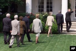 FILE - President George W. Bush waves as he is followed by members of his cabinet after he spoke on global warming in the Rose Garden of the White House, June 11, 2001. Two decades ago, the leading U.S. Senate proponent of taking action on global warming was Republican John McCain. Bush wasn't as zealous on the issue as his Democratic opponent for president in 2000, Al Gore, but he, too, talked of regulating carbon dioxide.