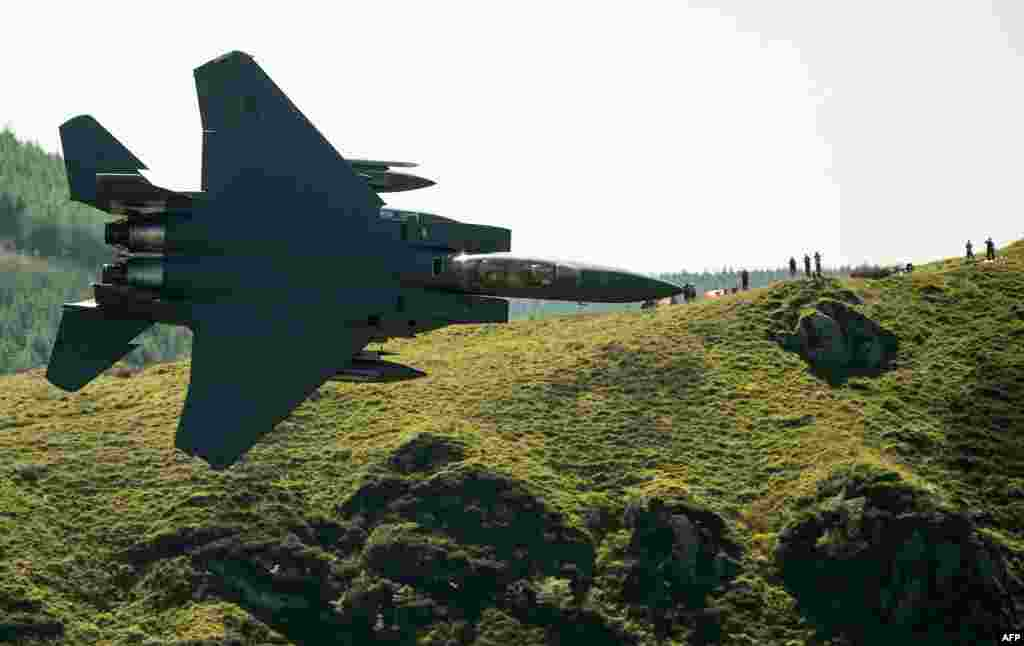 Military aircraft enthusiasts watch as a U.S. Air Force (USAF) F-15 fighter jet travels at a low altitude through the 'Mach Loop' series of valleys near Dolgellau, north Wales.