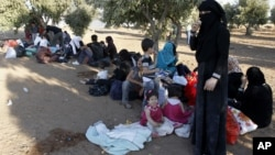 Newly-arrived Syrian refugee families rest after having crossed the border from Tal Shehab in Syria, through the Al Yarmouk River valley, to near Ramtha, Jordan, September 15, 2012.