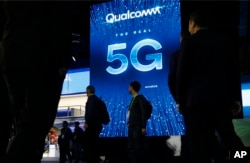 FILE - A sign advertises 5G at the Qualcomm booth at CES International in Las Vegas, Jan. 9, 2019.