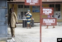 People walk inside the Yaba Mainland hospital compound where an Italian citizen who entered Nigeria on Tuesday from Milan on a business trip, the first case of the COVID-19 virus is being treated in Lagos Nigeria Friday, Feb. 28, 2020. (AP Photo)
