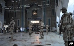 FILE - Pakistani paramilitary soldiers stand alert after a deadly suicide attack at the shrine of famous Sufi Lal Shahbaz Qalandar, in Sehwan, Pakistan, Feb. 16, 2017.