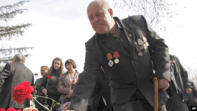 "A veteran ""liquidator"" at the Chernobyl nuclear reactor places flowers during a ceremony to honor victims of the Chernobyl disaster, in Krasnoyarsk, April 26, 2011"