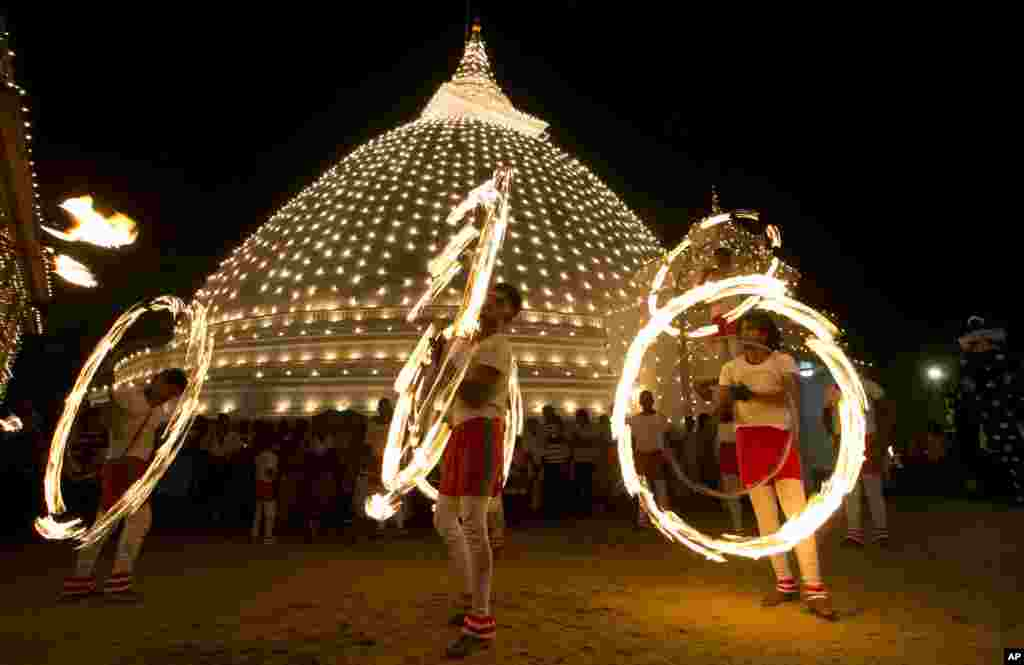 Sri Lankan fireball dancers are seen performing during the inauguration of the annual 'Duruthu Perahera' festival at Kelani Buddhist temple, in the outskirts of Colombo, Sri Lanka, Jan. 20, 2016.