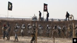 In this December 9, 2011, photo provided by the People's Mujahedeen Organization of Iran via AP, Iraqi police stand guard outside Camp Ashraf northeast of Baghdad (image authenticity cannot be independently verified).