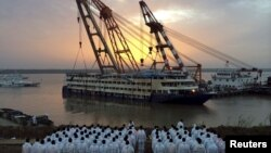 FILE - Rescue workers stand on the river bank as the capsized cruise ship Eastern Star is pulled out of the Yangtze against sunset, in Jianli, Hubei province, China, June 5, 2015.