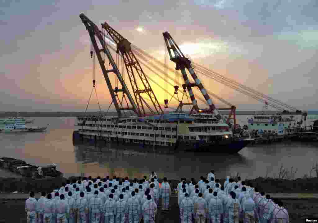 Rescue workers stand on the river bank as the capsized cruise ship Eastern Star is pulled out of the Yangtze at sunset in Jianli, Hubei province, China.
