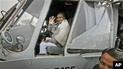 Indian Defense Minister A.K. Antony waves while sitting in the cockpit of an Indian Air Force Mi-17 V5 helicopter during its induction ceremony in New Delhi, India, Feb. 17, 2012.