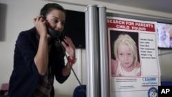 Một nhân viên của ''Smile of the child'' trước một tấm poster có hình bé Maria ở một trung tâm từ thiện ở Hy Lạp. (AP Photo/Thanassis Stavrakis)