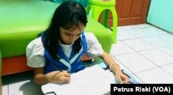 Seorang pelajar SD sedang mengerjakan ujian dari rumah di masa pandemi corona, 12 Mei 2020. (Foto: Petrus Riski/VOA)