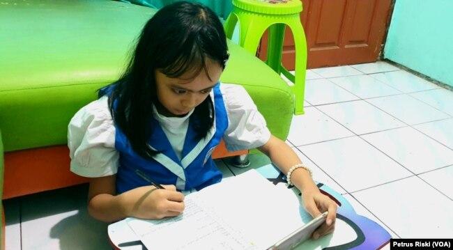 Seorang pelajar SD sedang mengerjakan ujian dari rumah di masa pandemi corona, di Surabaya, 12 Mei 2020. (Foto: Petrus Riski/VOA)