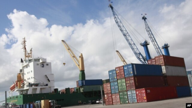 Shipping containers beside a cargo ship at the Port of Miami, Fla., Feb. 4, 2011 (file photo).