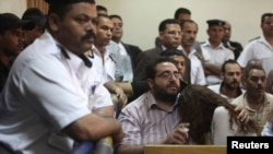 FILE - Friends of Egyptian suspects react as they listen to the judge's verdict at a court room during a case against foreign non-governmental organizations (NGOs) in Cairo, June 4, 2013