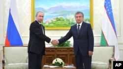 Uzbekistan's Prime Minister Shavkat Mirziyayev, right, poses for a photo with Russian President Vladimir Putin in Samarkand, Uzbekistan, Sept. 6, 2016. Putin came to offer condolences and visit the grave of Uzbekistan's late president, Islam Karimov.