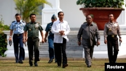 New Indonesian President Joko Widodo walks with heads of the military, police and intelligence to address the media at the presidential palace in Jakarta, Oct. 22, 2014.