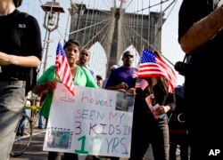 FILE - Martha Gualotuna of New York, center left, walks across New York's Brooklyn Bridge during a march and rally highlighting immigration reform, Oct. 5, 2013. Gualotuna is one of the 4 million immigrants who would have benefited from a program that was blocked June 23, 2016, by a decision of the Supreme Court.