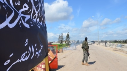 ສະມາຊິກກຸ່ມ Nusra ທີ່ເປັນເຄືອຂ່າຍ Al Qaida ຢືນເຝົ້າຢູ່ດ່ານກວດກາ ໃນເມືອງ Idlib.