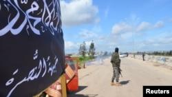 FILE - Members of al-Qaida's Nusra Front man a checkpoint in Idlib.