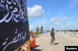 FILE - Members of al-Qaida's Nusra Front man a checkpoint in Idlib.