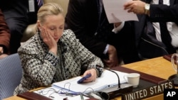FILE - Hillary Clinton, who at the time was U.S. secretary of state, checks her mobile phone after speaking to the U.N. Security Council in New York, March 12, 2012.