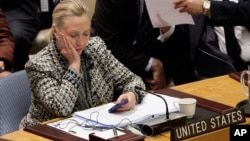 FILE - Then U.S. secretary of state Hillary Clinton checks her mobile phone after delivering an address to the Security Council at United Nations headquarters in New York, March 12, 2012.
