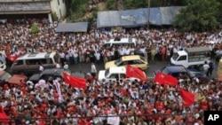 Các ủng hộ viên ăn mừng kết quả bầu cử trên màn hình phía trước trụ sở đảng NLD của lãnh tụ dân chủ Miến Ðiện Aung San Suu Kyi tại Yangon, ngày 1/4/2012