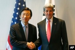 U.S. Secretary of State John Kerry, right, and South Korea's Foreign Minister Yun Byung-se shake hands during a meeting in Munich, Germany, prior to the start of the Munich Security Conference, Feb. 12, 2016.