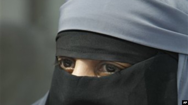 A woman dressed in a niqab, speaks with reporters during a press conference in Montreuil, east of Paris, 18 May 2010