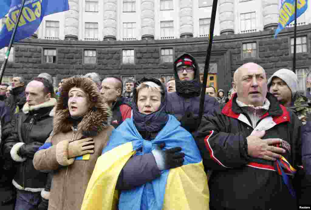 Supporters of Ukrainian EU integration sing and wave flags during a protest in front of the Ukrainian cabinet of ministers building in Kyiv,  Dec. 6, 2013.