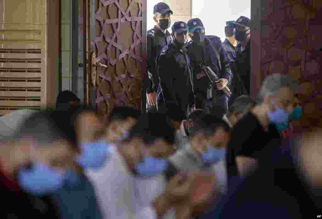Palestinian Hamas police stand guard at the entrance of a mosque as peopel attend the last Friday noon prayer of the holy month of Ramadan, in Gaza City.