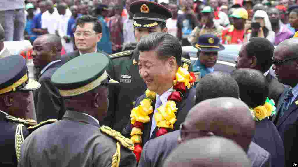 Chinese President Xi Jinping, centre, is welcomed upon his arrival in Harare, Zimbabwe, Tuesday, Dec. 1.2015. Jinping is in Zimbabwe for a two day State visit during which he is set to sign some bilateral agreements aimed at strengthening relationships between the two countries.