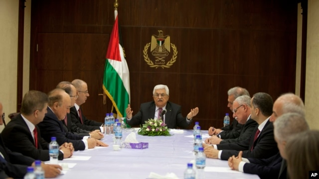 Palestinian President Mahmoud Abbas (C) meets with ministers of the unity government, in the West Bank city of Ramallah June 2, 2014. Abbas swore in a Palestinian unity government on Monday under a reconciliation deal with Hamas.