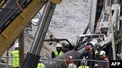 Các công nhân cứu hộ đặt ống thép vào lối thoát để bảo đảm rằng một khoang cứu hộ nhỏ sẽ không bị vỡ khi di chuyển lên xuống hố sâu để đưa từng thợ mỏ lên mặt đất