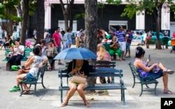 FILE - People surf the Internet at a Wi-Fi hotspot in Havana, Cuba, Nov. 25, 2015.