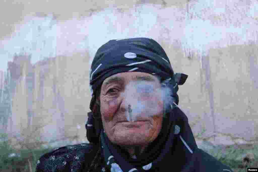 Seorang perempuan beristirahat sambil merokok setelah dievakuasi oleh Pasukan Demokratis Suriah (SDF) dari kota Manbij yang dikuasai ISIS di Aleppo, Suriah (12/8). (Reuters/Rodi Said)