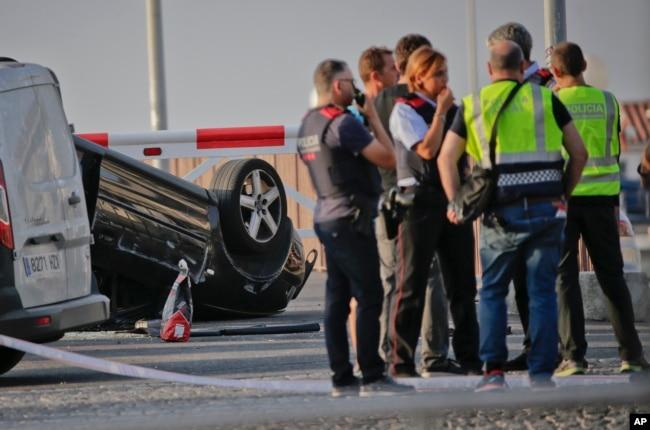 Zyrtarët e policisë flasin pranë një makine të përmbysur në vendin ku terroristët u kapën nga policia në Cambrils, Spanjë, më 18 gusht 2017. Forcat policore për rajonin e Katalonjës Spanjolle thanë se pesë të dyshuar u qëlluan dhe u vranë në qytetin turistik Cambrils