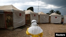 A health worker wearing Ebola protection gear, prepares to enter the Biosecure Emergency Care Unit at the Alliance for International Medical Action ebola treatment center in Beni, DRC. (March 30, 2019)
