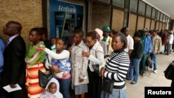 People queue to withdraw cash outside a bank in Harare, Zimbabwe, Nov. 28, 2017.
