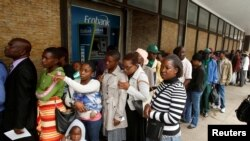 FILE: People queue to withdraw cash outside a bank in Harare, Zimbabwe, Nov. 28, 2017.