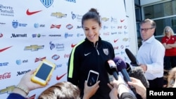 美国女子足球队员卡莉·劳埃德在训练场地与记者交谈。