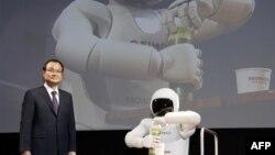 """Pemimpin perusahaan Honda Motor Co. Takanobu Ito berdiri di dekat robot """"Asimo"""" saat menggelar konferensi pers dalam Tokyo Motor Show, Jepang tahun 2011 (Foto: dok). Takanobu Ito, akan mundur dari posisinya sebagai direktur perusahaan tersebut, menyusul kemelut skandal kantong udara mobil yang buruk, Senin (23/2)."""