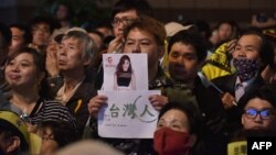 A supporter of Taiwan's Democratic Progressive Party holds up a placard of Chou Tzu-yu, who was forced to apologize after waving the Taiwanese flag
