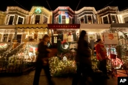 In this Dec. 10, 2012 photo, people walk past holiday decorations on homes on 34th Street in the Hampden neighborhood of Baltimore.