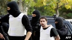 Grčka policija odvodi na saslušanje jednog od osumnjičenih za slanje paketa