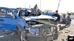 一名伊拉克警察在检查汽车炸弹爆炸现场
