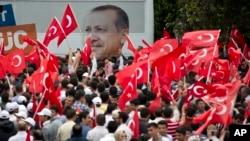 Para pendukung melambai-lambaikan bendera Turki dengan latar belakang gambar Perdana Menteri Recep Tayyip Erdogan saat mereka menunggu kedatangannya di Ankara (9/6).
