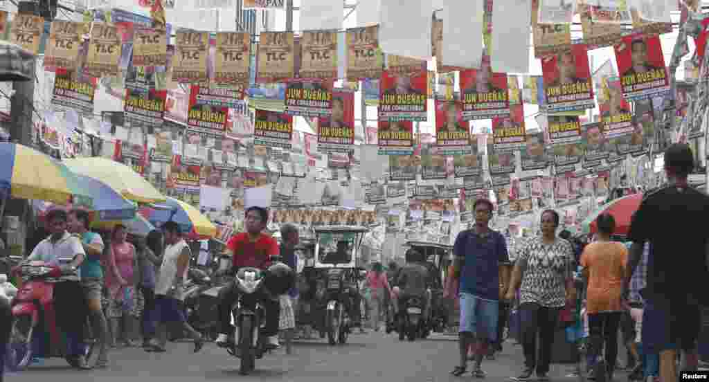 Election posters for the midterm elections hang along a street as residents walk to a polling precinct in Taguig, Metro Manila, May 13, 2013.