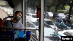 Seorang penumpang tidur di dalam bus Trans Jakarta dengan latar belakang kemacetan jalan raya Jakarta.(Reuters/Beawiharta)