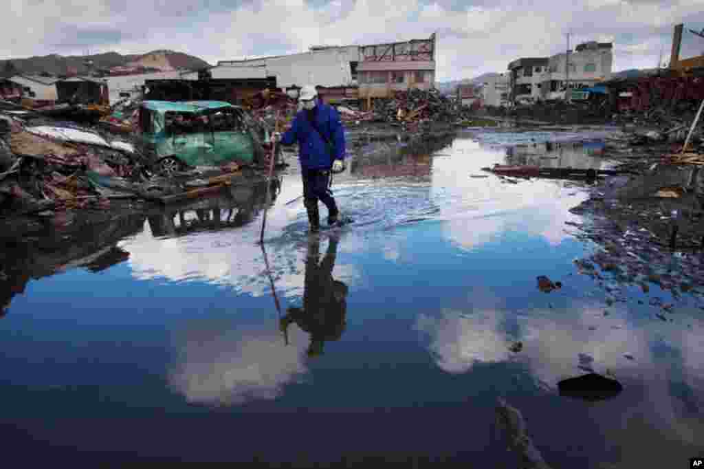 March 27: A man walks through a flooded street in the ravaged city of Kesennuma, northeastern Japan. (AP Photo/David Guttenfelder)