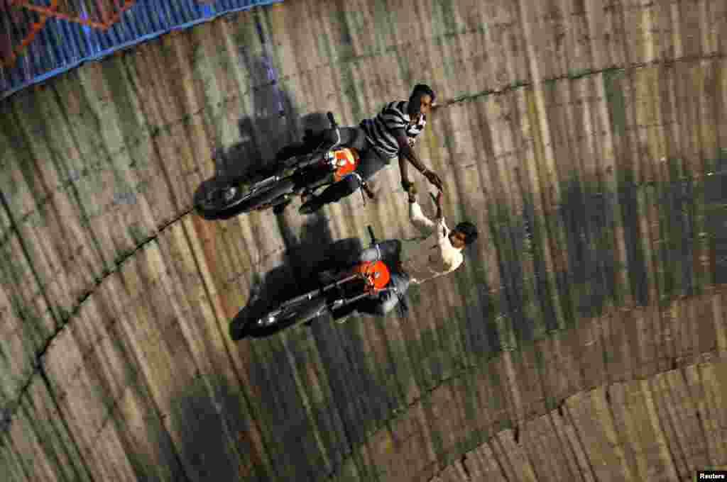 """Những người biểu diễn những pha mạo hiểm đi xe gắn máy trên bức tường của """"Giếng Tử thần,"""" tại một hội chợ ở vùng ngoại ô của thành phố Bengaluru, Ấn Độ."""
